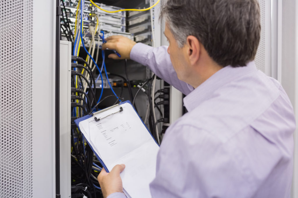 Photo of man reaching into a rack of electronic equipment, holding a clipboard