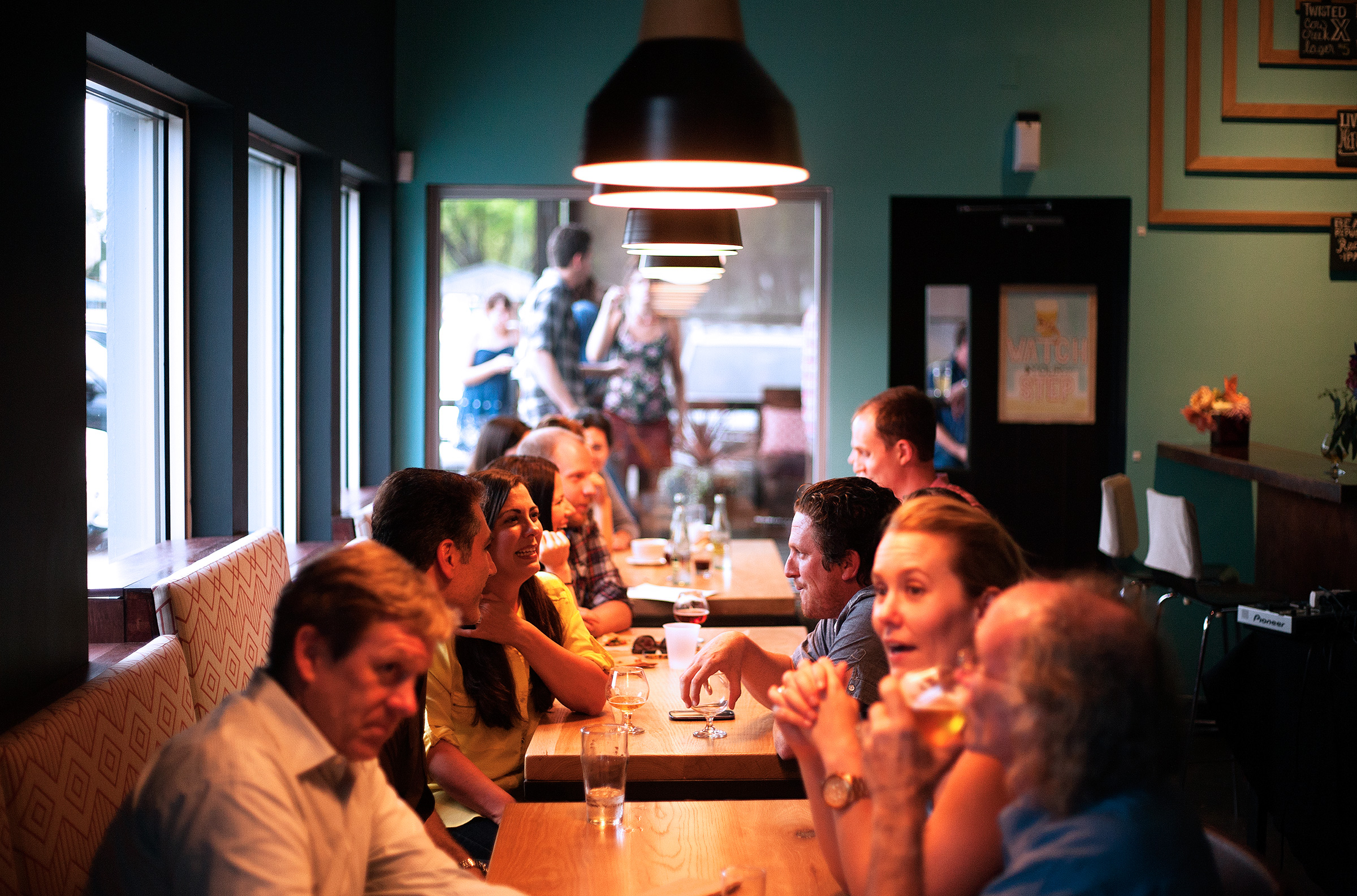 Photo of several tables of people chatting, drinking at a restaurant