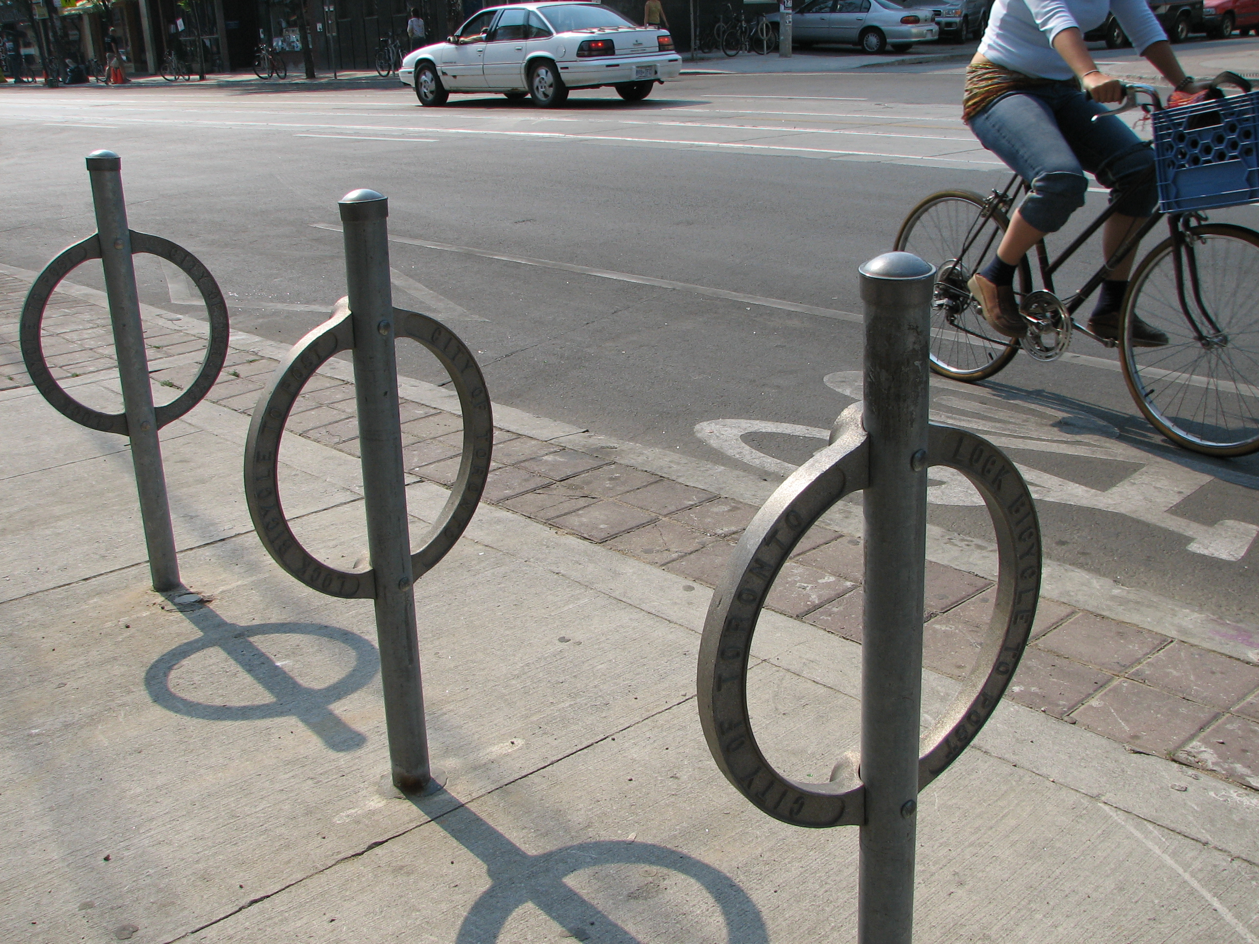 A photograph of a bike path on College Street in Toronto's Little Italy district. There is a bicycle on the path, and in the foreground there are locking poles.