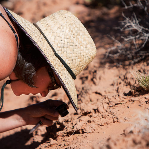 Photo of woman wearing straw hat bent close to the ground inspecting the soil using a jeweler's loop